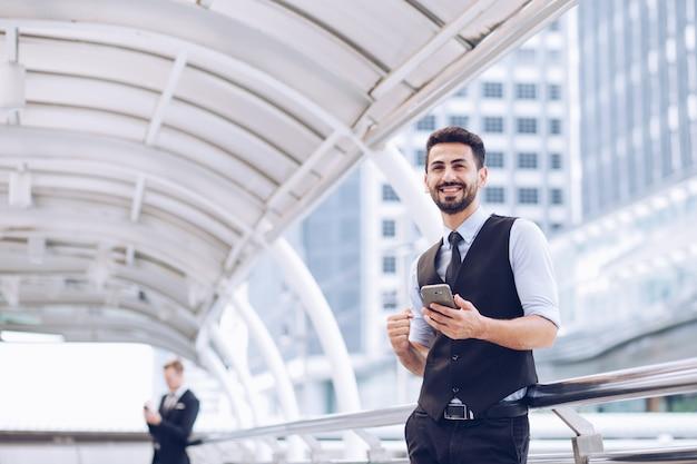 Biznesmen spojrzał na swoją twarz z lekką brodą, trzymając dłonie w smartfonie,