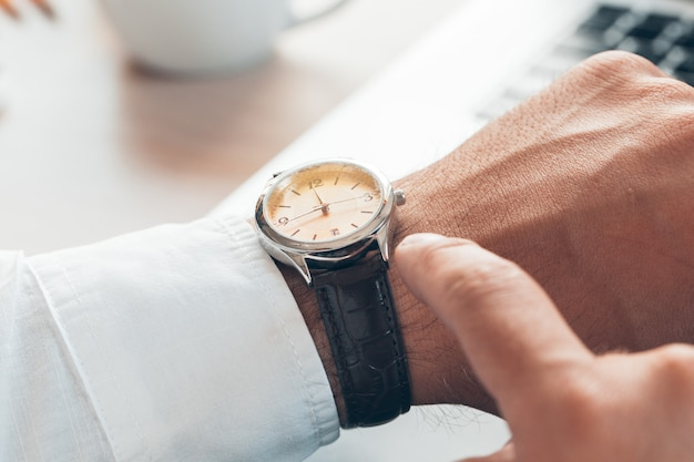 Biznesmen sprawdza czas na jego zegarka zakończeniu up