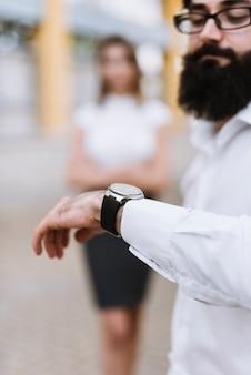 Biznesmen sprawdza czas na nadgarstku zegarku z zamazanym żeńskim kolegą w tle