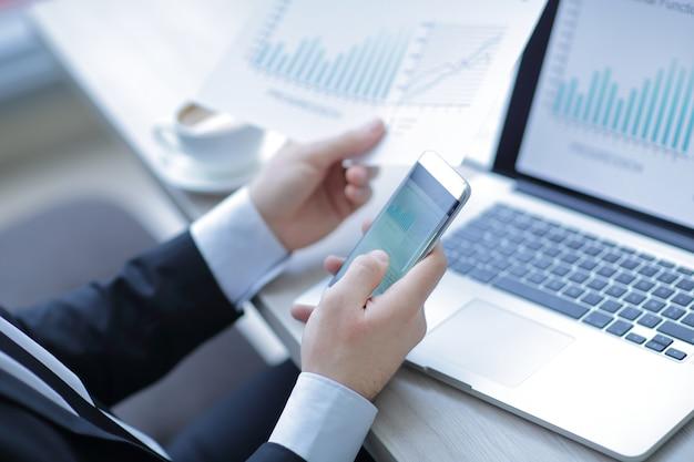 Biznesmen sprawdza dane finansowe za pomocą smartfona.