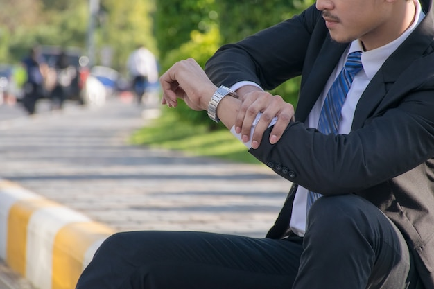 Biznesmen sprawdza godzinę i czeka na spotkanie