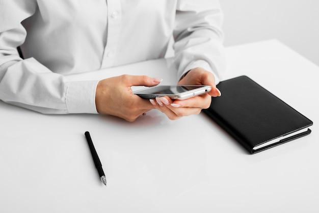 Biznesmen sprawdza jego telefon przy biurem