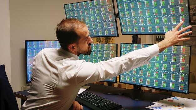 Biznesmen sprawdza swoje inwestycje na giełdzie, podczas gdy firma traci pieniądze.