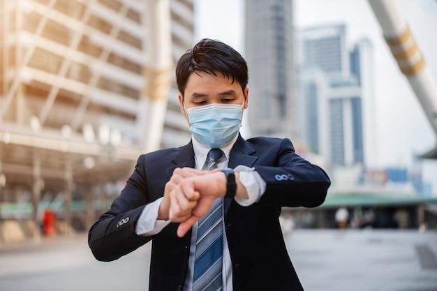 Biznesmen sprawdzający czas na zegarku i noszący maskę medyczną podczas pandemii koronawirusa w mieście