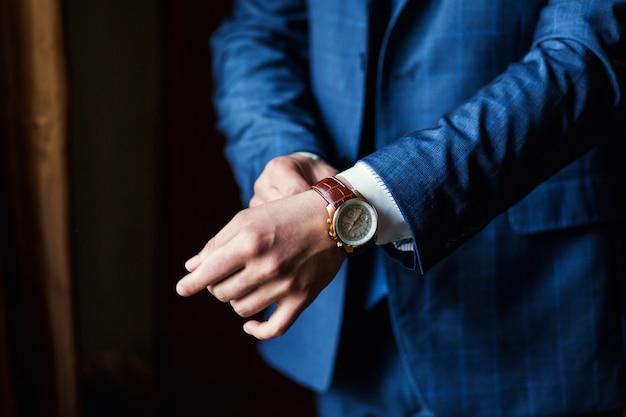 Biznesmen sprawdzanie czasu na jego zegarek na rękę, człowiek wprowadzenie zegara na rękę, przygotowuje się rano przed ceremonią ślubną