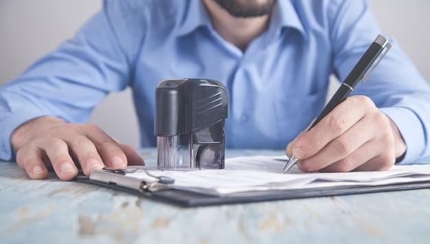 Biznesmen stawia pieczęć na dokumencie. pisanie w dokumencie