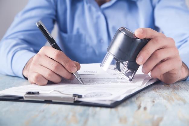 Biznesmen stawia pieczęć na dokumentach w biurze.