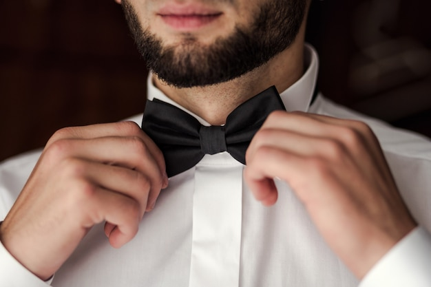 Biznesmen, stawiając na muszkę, ubrania motyla człowieka, przygotowuje się rano przed ceremonią ślubną. moda męska