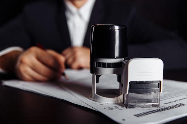 Biznesmen stawianie pieczęci na dokumentach w biurze. pomysł na biznes