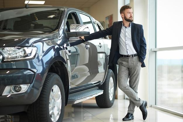 Biznesmen stoi blisko dżipa w samochodowym centrum.