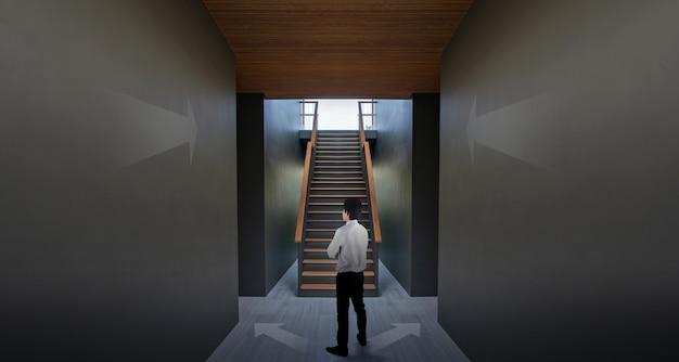 Biznesmen stoi blisko strzała na czerni ścianie i schody, pojęcie dokonywać twój sukces