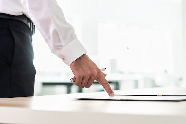 Biznesmen stojąc przy biurku, wskazując na dokument, wniosek lub umowę, trzymając pióro.