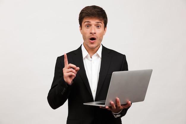 Biznesmen stojący na białym tle posiadania komputera przenośnego ma pomysł.