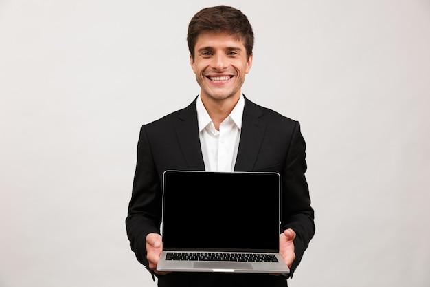 Biznesmen stojący na białym tle posiadania komputera przenośnego pokazując pusty wyświetlacz.