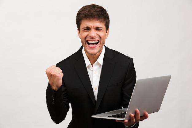 Biznesmen stojący na białym tle posiadania komputera przenośnego zrobić gest zwycięzcy.