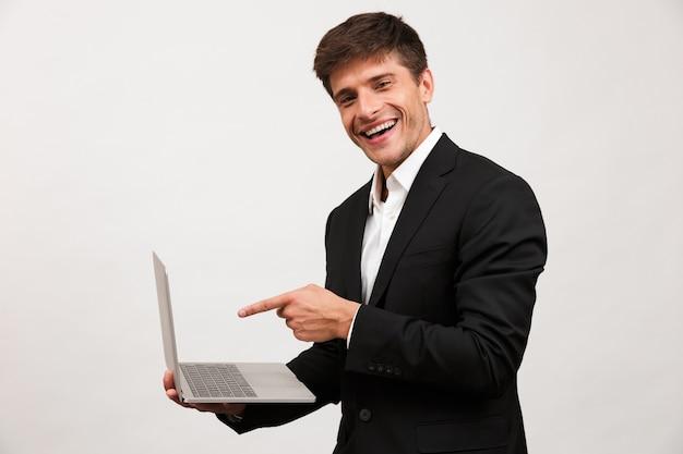 Biznesmen stojący na białym tle przy użyciu komputera przenośnego, wskazując.