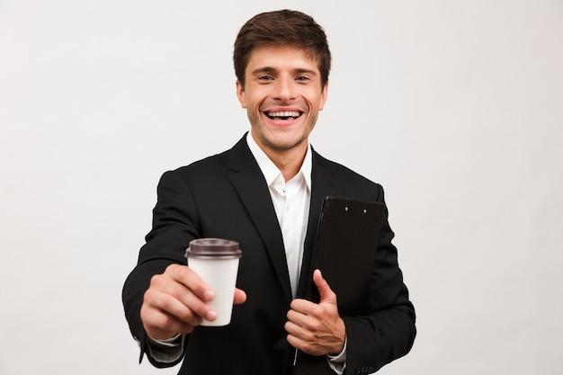 Biznesmen stojący na białym tle trzymając schowek do picia kawy.