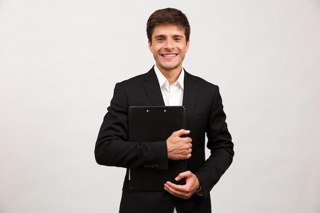 Biznesmen stojący na białym tle trzymając schowek