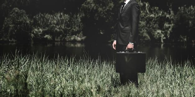 Biznesmen stojący na trawie na zewnątrz