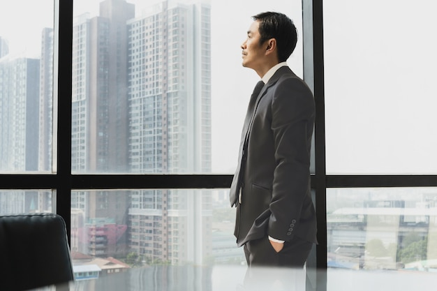 Biznesmen stojący obok okna, patrząc na widok z boku