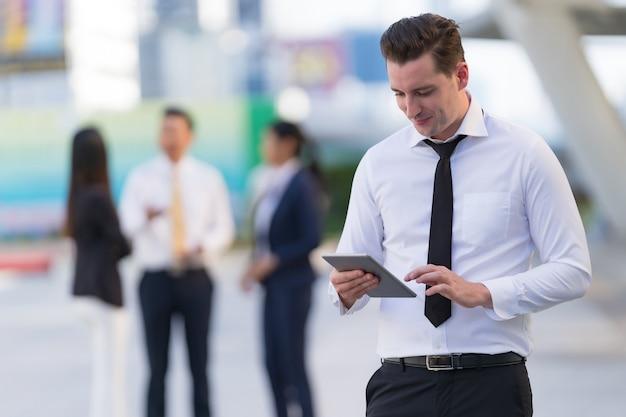 Biznesmen stojący przed nowoczesnymi budynkami biurowymi za pomocą cyfrowego tabletu