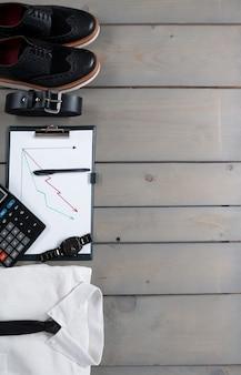 Biznesmen, strój do pracy na szarym tle drewnianych. biała koszula z czarnym krawatem, zegarkiem, paskiem, półbutami, planszetką i kalkulatorem.