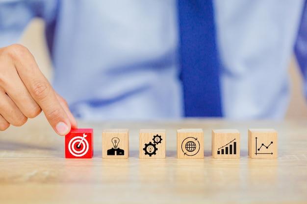 Biznesmen strony wprowadzenie blok sześcian drewna na górze z koncepcją sukcesu cel.