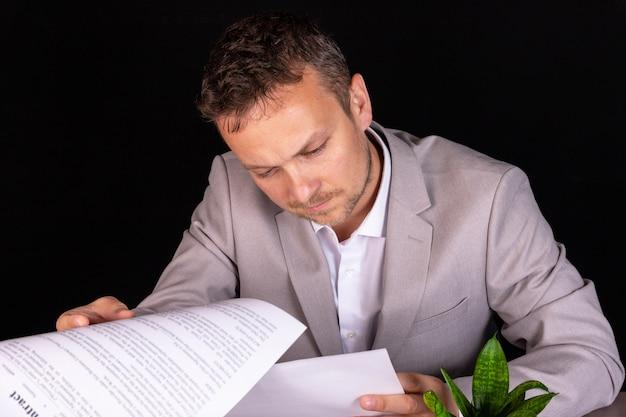 Biznesmen studiuje dokument papierowy z poważną miną, gdy siedzi przy biurku w biurze