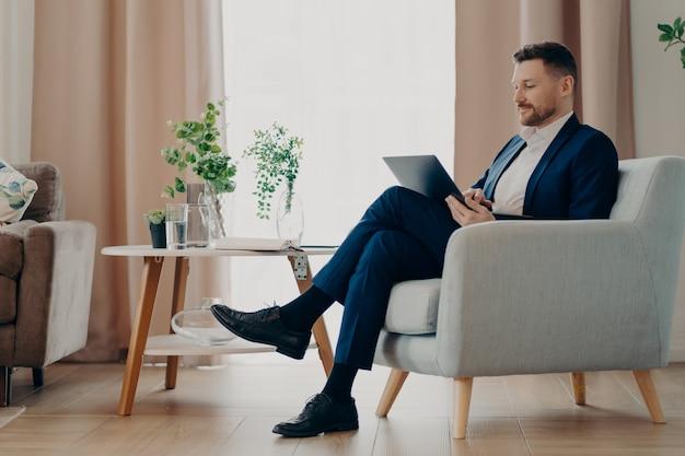 Biznesmen sukcesu w stroju wizytowym siedzi w wygodnym fotelu korzysta z nowoczesnego laptopa przygotowuje projekt online pozy na tle wnętrza analizuje wskaźniki finansowe kontroluje rozwój firmy