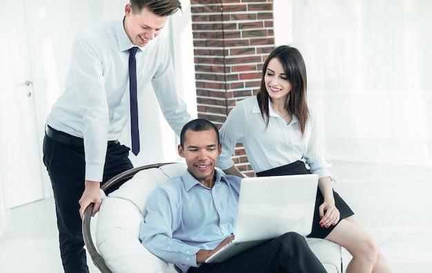 Biznesmen sukcesu ze swoimi asystentami w dyskusji o informacjach z życia laptopa.biurowego