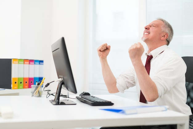 Biznesmen świętuje sukces przed komputerem
