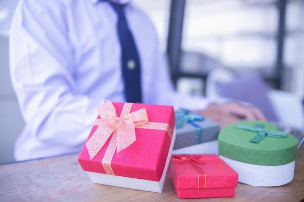 Biznesmen szczęśliwych bożych narodzeń prezenta pudełko od klienta w biurze.