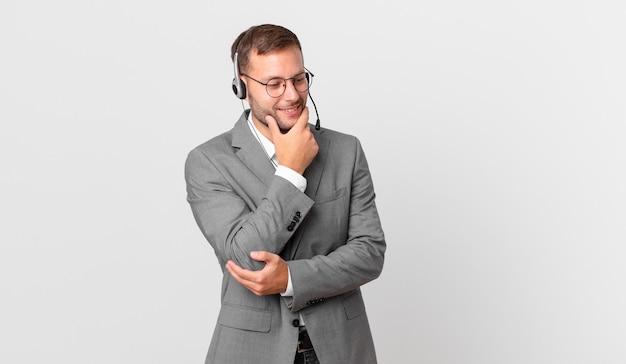 Biznesmen telemarketera uśmiechający się ze szczęśliwym, pewnym siebie wyrazem twarzy z ręką na brodzie