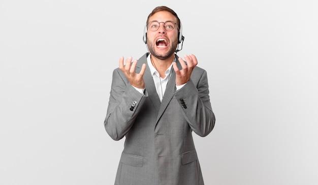 Biznesmen telemarketera wyglądający na zdesperowanego, sfrustrowanego i zestresowanego