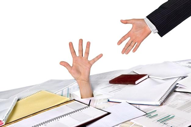 Biznesmen tonący w papierkowej robocie sięgający po pomoc i wsparcie