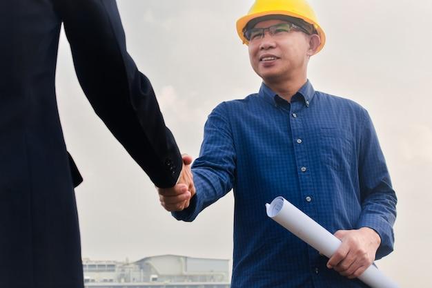 Biznesmen trząść ręki inżyniera budowy sukcesu budowy budynku projekt, ręki trząść zgoda