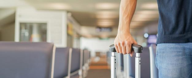 Biznesmen trzyma bagaż w bramie lotniska
