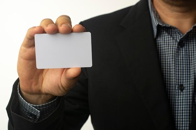 Biznesmen trzyma białą wizytówkę.