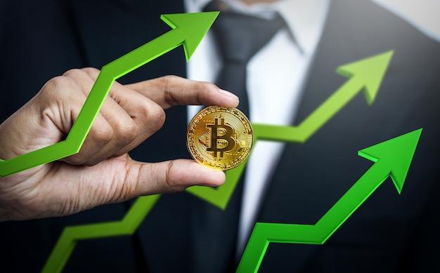Biznesmen trzyma bitcoin z zieloną 3d strzała up. cena bitcoinów rośnie