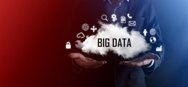 Biznesmen trzyma chmurę z napisem, słowo big data. kłódka, mózg, człowiek, planeta, wykres, lupa, koła zębate, chmura, siatka, dokument, list, ikona telefonu.