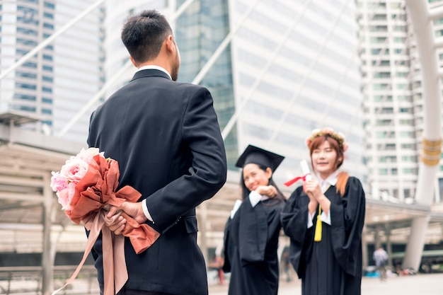 Biznesmen trzyma chowając bukiet kwiatów za gratulacje dla młodej kobiety, która ukończyła studia licencjackie