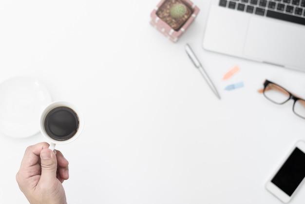 Biznesmen trzyma czarną filiżankę do picia na ciężko pracujących rano