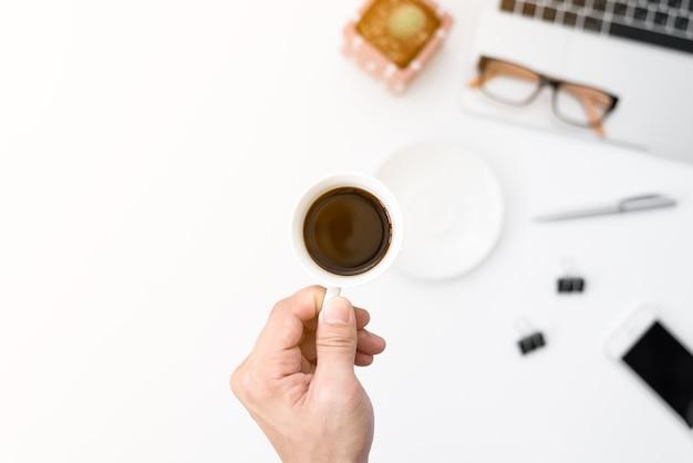 Biznesmen trzyma czarną filiżankę do picia na ciężko pracujących rano.