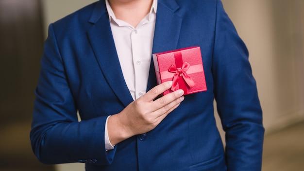 Biznesmen trzyma czerwonego prezenta pudełko