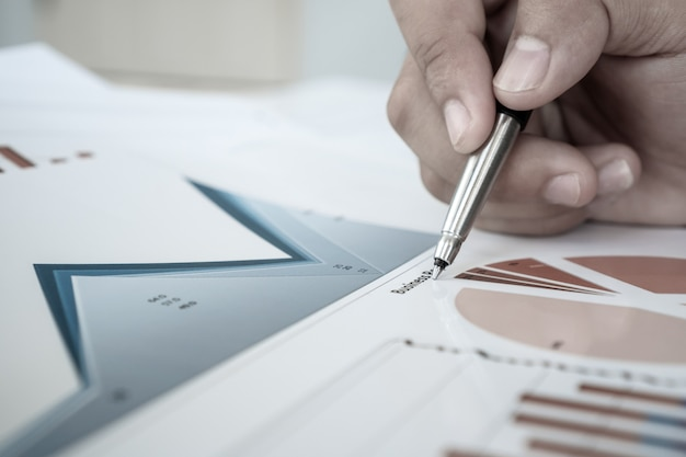 Biznesmen trzyma długopis do czytania podpisywania dokumentów papierkowej roboty z raportem marketingowym wykresu lub raportów biznesowych w biurze.