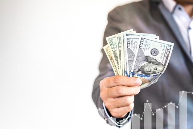 Biznesmen trzyma dolara amerykańskiego banknot z technologia cyfrowym wzrostowym wykresem