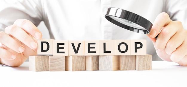 Biznesmen trzyma drewniany blok. zegarek biznesmen na drewnianych kostkach z tekstem planowanie. rynek finansowy. finansowanie