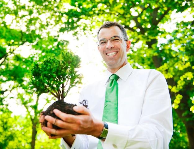 Biznesmen trzyma drzewa zasadzać w lesie.