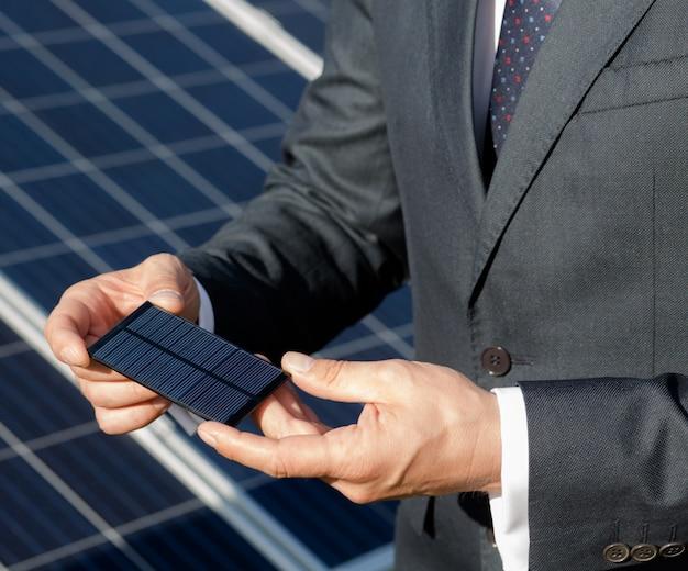 Biznesmen trzyma element fotowoltaiczny w jego ręce.