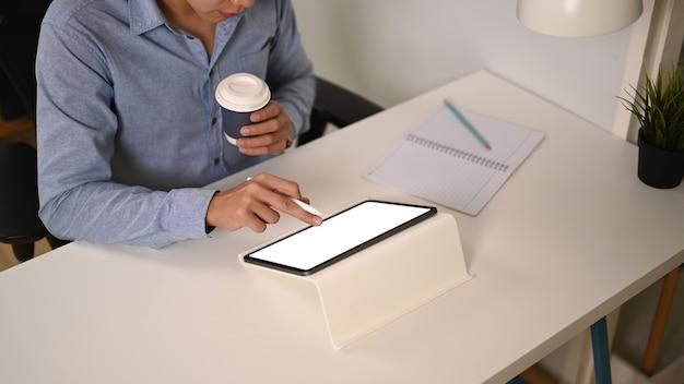 Biznesmen trzyma filiżankę kawy i pracuje w biurze.